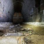 Zdjęcie przedstawiające wnętrze jednego z korytarzy w bunkrach, oświetlonego za pomocą latarki.